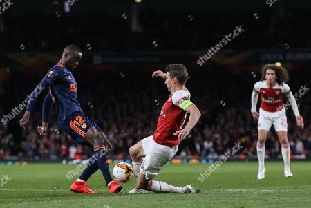 Laurent Koscielny of Arsenal and Mouctar Diakhaby of Valencia challenge for the ball