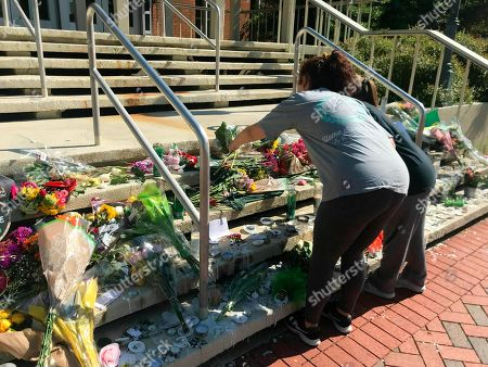Stock Image of Mourners pause to look at a variety of memorials left at Kennedy Hall at the University of North Carolina at Charlotte on . A gunman opened fire at Kennedy on Tuesday, killing two and wounding four