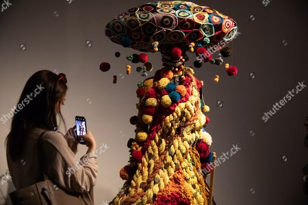Stock Picture of A visitor takes photos of a mannequin in a costume during the 'Tim Yip: Mirror' exhibition at the Today Art Museum in Beijing, China, 03 May 2019. Tim Yip is an artist, costume designer, and art director for stage and film. The exhibition 'Tim Yip: Mirror' shows various expression formats of art using photography, video, installation and sculpture. The exhibition runs from 13 April to 21 July 2019.
