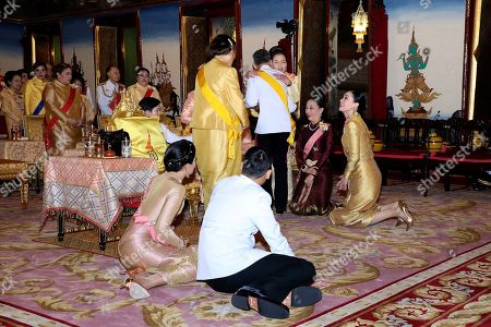 Released by Bureau of the Royal Household, Thailand's King Maha Vajiralongkorn, center, hugs his sister Princess Ubolratana, with Royal family and Queen Suthida, sitting at right, before make the religious ceremony at Grand Palace in Bangkok, Thailand. The coronation ceremony for 66-year-old King Maha Vajiralongkorn, also known as King Rama X, will be held on May 4-6, 2019