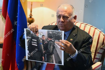 Venezuelan Ambassador to Spain, Mario Isea, poses with an undated photo displaying Venezuelan opposition leader Leopoldo Lopez with officers of the National Guard during an interview with Spanish News Agency EFE in Madrid, Spain, 03 May 2019. Isea said that Venezuela is claiming Spain to hand over Venezuelan opposition leader Leopoldo Lopez, who sought refuge at the Spanish ambassador's residence in Caracas. Spain's Foreign Minister said that the embassy would not hand Lopez over to the Venezuelan authorities despite an arrest order issued by the Supreme Court, and that  Lopez would remain a 'guest' of the embassy.