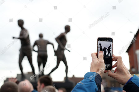 Stock Image of Fans take photographs of the Holy Trinity statue of former Everton players Howard Kendall, Colin Harvey and Alan Ball is displayed outside the stadium