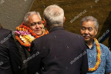 Mike McCartney, center, flanked by Gov. David Ige, right, is congratulated by senators on the Senate floor at the Hawaii State Capitol in Honolulu on after senators confirmed McCartney to lead the state Department of Business, Economic Development and Tourism