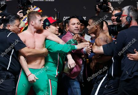 Oscar De La Hoya, center, gets between Canelo Alvarez, left, and Daniel Jacobs during a weigh-in for the middleweight title boxing match between Alvarez and Jacobs, in Las Vegas. The two are scheduled to fight Saturday in Las Vegas