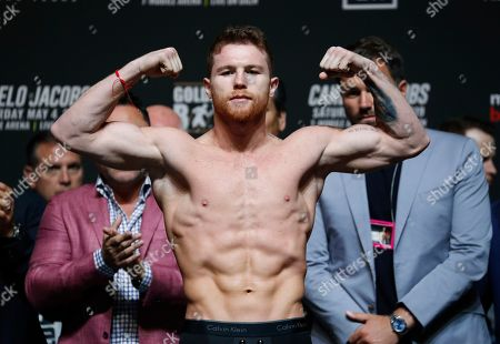 Canelo Alvarez poses on the scale during a weigh-in for his middleweight title boxing match against Daniel Jacobs, in Las Vegas. The two are scheduled to fight Saturday in Las Vegas