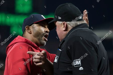 Washington Nationals manager Dave Martinez, left, meets with home plate umpire Bill Miller during the fourth inning of a baseball game against the Philadelphia Phillies, in Philadelphia