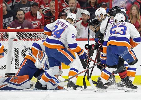 Stock Image of Sebastian Aho, Robin Lehner, Casey Cizikas, Adam Pelech, Scott Mayfield. Carolina Hurricanes' Sebastian Aho scores against New York Islanders goalie Robin Lehner while Islanders' Scott Mayfield (24) and Casey Cizikas (53) defend with Adam Pelech during the first period of Game 4 of an NHL hockey second-round playoff series in Raleigh, N.C