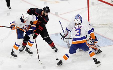 Carolina Hurricanes' Jordan Staal (11) struggles with New York Islanders' Scott Mayfield (24) and Adam Pelech (3) during the third period of Game 4 of an NHL hockey second-round playoff series in Raleigh, N.C., . Carolina won 5-2 to advance the Eastern Conference final