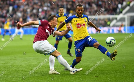 Mark Noble of West Ham clears under pressure from Ryan Bertrand of Southampton