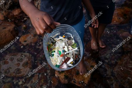 Stock Image of A South African student holds a container of small plastic items picked out of Decorator Sea Urchins during a beach clean up of the inter-tidal zone of Dalebrook tidal pool in Kalk Bay, Cape Town, South Africa, 04 May 2019. The cleanup was organized by Oceano Reddentes, a South African Non-Profit Organization teaching ocean users to collect plastic to make Ecobricks which are then used to build homes for the homeless. Plastic pollution has reached an epidemic proportion. According to an Ellen MacArthur Foundation report, there will be more plastic in the ocean than fish by 2050. Africa is one of the most affected continents due to its extensive coastline and underdeveloped waste systems allowing plastic waste to easily enter the ocean. The rapid growth of plastic production in the three biggest areas the European Union, China and the US particularly in single-use plastics is recognized as one of the greatest risks facing the environment and mankind. Efforts at recycling and plastic waste education are on the rise on the African continent with many programs being initiated by youth groups who view the problem as the biggest environmental challenge facing the new generation.