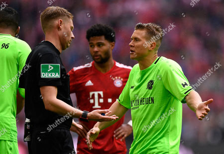 Stock Photo of Hannover's Matthias Ostrzolek (R) talks to Referee Christian Dingert (L) during the German Bundesliga soccer match between Bayern Munich and Hannover 96 in Munich, Germany, 04 May 2019.