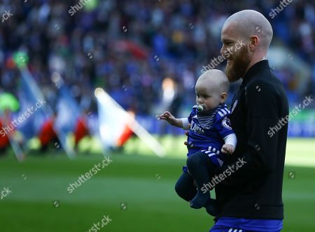 Aron Gunnarsson of Cardiff City with his baby as he walks out for his final home appearance for the club