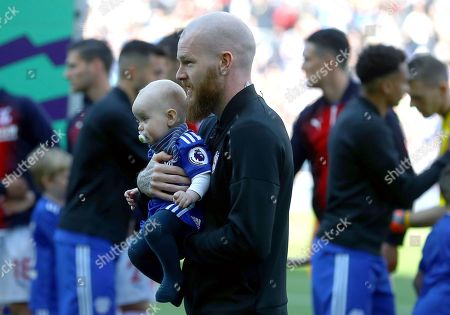 Aron Gunnarsson of Cardiff City walks out with his baby before his last home appearance for the club