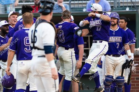 Western Carolina's Andrew Robinson (17) leaps as he celebrates a homreun by Matthew Koehler (10) as Koehler approaches the dugout with Georgia Tech catcher Kyle McCann (16) looks on during an NCAA college baseball game, in Atlanta