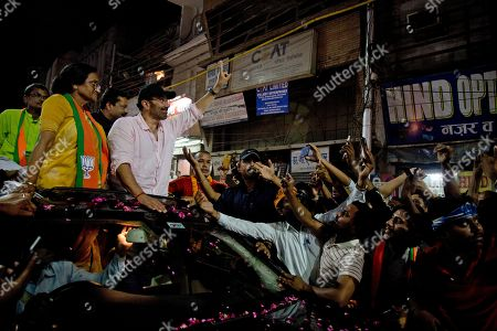 Bollywood actor and India's ruling Bharatiya Janata Party (BJP) candidate Sunny Deol, top right, displays the victory symbol during an election campaign rally for party colleague Rita Bahuguna Joshi, left, in Prayagraj, India