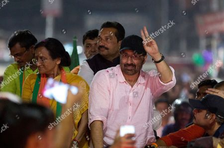 Bollywood actor and India's ruling Bharatiya Janata Party (BJP) candidate Sunny Deol, right, displays the victory symbol during an election campaign rally for party colleague Rita Bahuguna Joshi, left, in Prayagraj, India