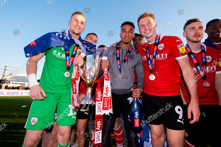 Jack Walton of Barnsley, Jacob Brown of Barnsley and Cauley Woodrow celebrate after the final whistle of the match after Barnsley secure automatic promotion to the Sky Bet Championship