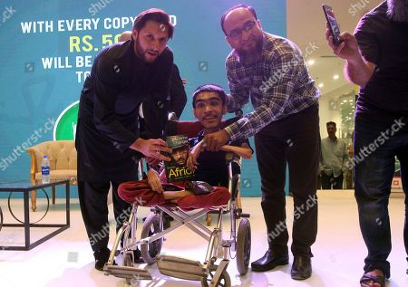 Retired Pakistani cricketer Shahid Afridi, left, presents a copy of his biography to a physically challenge boy during its book launching ceremony at a shopping mall in Karachi, Pakistan