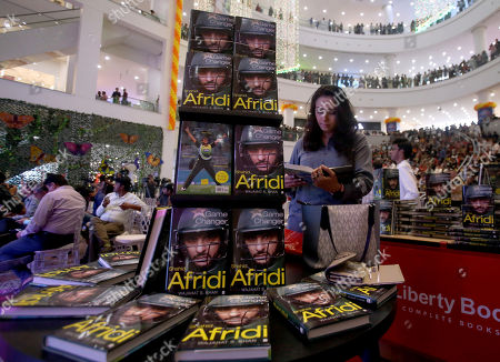 A journalist reads a biography of retired Pakistani cricketer Shahid Afridi displaying at a shopping mall during Afridi's book launching ceremony in Karachi, Pakistan