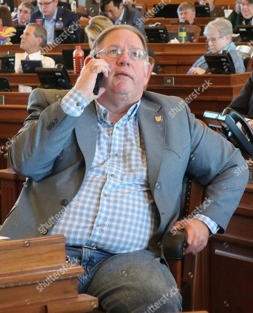 Stock Picture of Kansas House Majority Leader Dan Hawkins, R-Wichita, talks on his cell phone and watches a vote-tallying board as the House passes a proposed state budget at the Statehouse, in Topeka, Kan. The budget passed after an effort to block it in hopes of forcing a debate on Medicaid expansion collapsed
