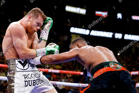 Daniel Jacobs, right, hits Canelo Alvarez, of Mexico, in a middleweight title boxing match, in Las Vegas