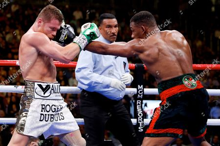 Daniel Jacobs, right, hits Canelo Alvarez, of Mexico, during a middleweight title boxing match, in Las Vegas
