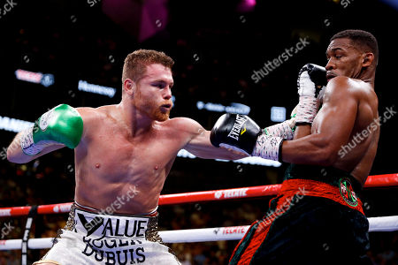Canelo Alvarez, left, of Mexico, throws a left at Daniel Jacobs during a middleweight title boxing match, in Las Vegas