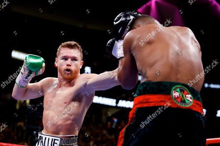Canelo Alvarez, left, of Mexico, tries to hit Daniel Jacobs with a left during a middleweight title boxing match, in Las Vegas