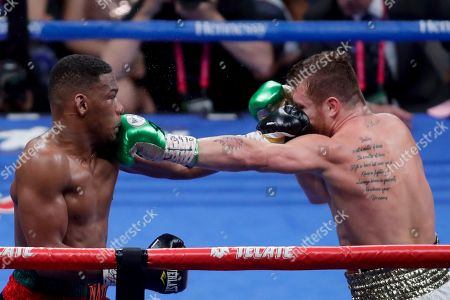 Canelo Alvarez, right, of Mexico, and Daniel Jacobs trade blows during a middleweight title boxing match, in Las Vegas