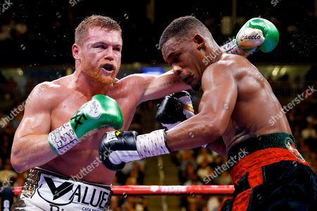 Canelo Alvarez, left, of Mexico, fights Daniel Jacobs in a middleweight title boxing match, in Las Vegas