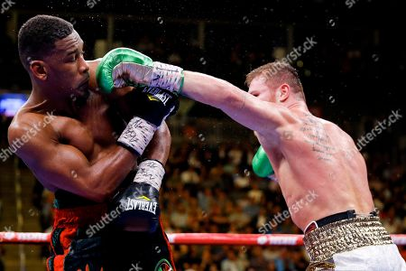 Canelo Alvarez, right, of Mexico, tries to hit Daniel Jacobs with a left during a middleweight title boxing match, in Las Vegas