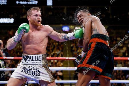Canelo Alvarez, left, of Mexico, hits Daniel Jacobs during a middleweight title boxing match, in Las Vegas