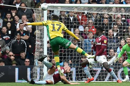 Stock Image of Norwich City midfielder Emi Buendia (17) takes a shot at goal defended by Aston Villa defender Alan Hutton (21) during the EFL Sky Bet Championship match between Aston Villa and Norwich City at Villa Park, Birmingham