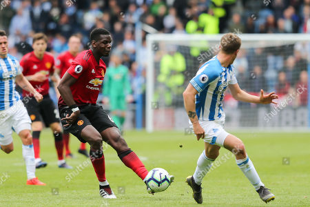 Manchester United midfielder Paul Pogba (6) plays the ball as Huddersfield Town defender Erik Durm (37) tries to block it during the Premier League match between Huddersfield Town and Manchester United at the John Smiths Stadium, Huddersfield