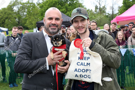 Stock Photo of Judge Marc Abraham, the TV vet, with Zoe the Pomchi and owner Harry, winners of the best rescue dog category (Zoe was rescued from New Mexico) at the All Dogs Matter Bark Off charity dog show, Hampstead Heath, London, England. Cute dogs took part in several categories of this annual dog show which is run by the charity which houses and rehomes dogs in London and finds homes for dogs from overseas. Dogs competed to be cutest pup, best rescue and more. More information at www.alldogsmatter.co.uk