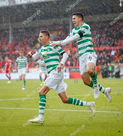 Mikael Lustig of Celtic is chased by team mate Tom Rogic, as he celebrates scoring to give them a 0-1 lead.