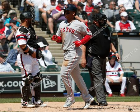 Stock Image of Boston Red Sox's Rafael Devers, center, scores in front of Chicago White Sox catcher Welington Castillo, left, and umpire Fieldin Culbreth during the second inning of a baseball game in Chicago