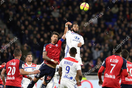 Lyon's Jason Denayer, center, challenges for the ball with Lille's Jose Miguel Da Rocha Fonte, left, during a French League One soccer match in Decines, near Lyon, central France
