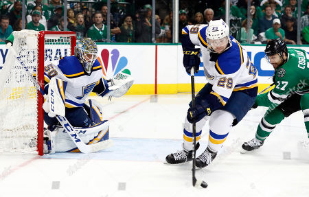 St. Louis Blues' Vince Dunn handles the puck as goaltender Jordan Binnington (50) and Dallas Stars' Andrew Cogliano watch during the first period in Game 6 of an NHL second-round hockey playoff series, in Dallas