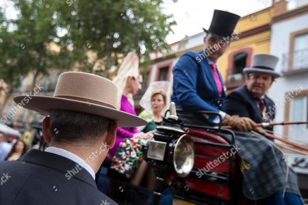 A man who judges the carriage reviews the Sevillana women in fancy dresses and 'mantillas' (lace hair coverings) inside a horse drawn carriage as they parade through Seville, Spain, 05 May 2019, during the day of the 'enganches' or carriages, as part of the Feria de Abril. This Spring Fair is a week of bullfights, horses, fancy dress, Flamenco dancing and music and the usual mounts of fine foods and lots of drinking.