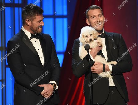 Stock Picture of Jesse Palmer, Brandon McMillan. Jesse Palmer, left, and Brandon McMillan, while holding a dog, present the award for outstanding entertainment talk show host at the 46th annual Daytime Emmy Awards at the Pasadena Civic Center, in Pasadena, Calif
