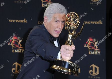 "Alex Trebek poses in the press room with the award for outstanding game show host for ""Jeopardy!"" at the 46th annual Daytime Emmy Awards at the Pasadena Civic Center, in Pasadena, Calif"