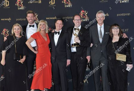 """Jesse Palmer, second from left, and the cast and crew of """"DailyMailTV"""" pose in the press room with the award for outstanding entertainment news program at the 46th annual Daytime Emmy Awards at the Pasadena Civic Center, in Pasadena, Calif"""