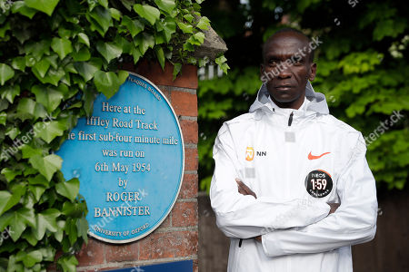 Marathon world record holder Kenya's Eliud Kipchoge poses for photographers beside a heritage blue plaque for the achievement of British athlete Roger Bannister, who in 1954 ran to become the first person ever to break the four minute mile barrier at the Iffley Road Track, in Oxford, England, . Eliud Kipchoge has funding from Britain's richest man, Jim Ratcliffe, who founded chemicals group INEOS, for his bid to break the two-hour marathon barrier again later this year