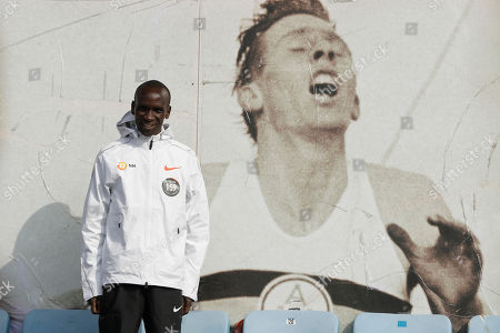 Marathon world record holder Kenya's Eliud Kipchoge poses for photographers next to an image of British athlete Roger Bannister, who in 1954 ran to become the first person ever to break the four minute mile barrier, at the Iffley Road Track, in Oxford, England, . Eliud Kipchoge has funding from Britain's richest man, Jim Ratcliffe, who founded chemicals group INEOS, for his bid to break the two-hour marathon barrier again later this year