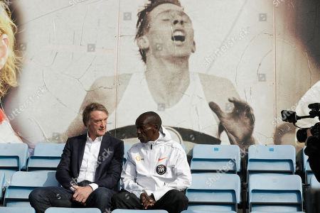 Marathon world record holder Kenya's Eliud Kipchoge and Britain's richest person Jim Ratcliffe pose for photographers next to an image of British athlete Roger Bannister, who in 1954 ran to become the first person ever to break the four minute mile barrier, at the Iffley Road Track, in Oxford, England, . Eliud Kipchoge has funding from Britain's richest man, Jim Ratcliffe, who founded chemicals group INEOS, for his bid to break the two-hour marathon barrier again later this year