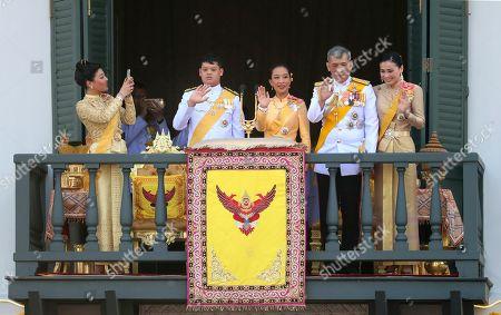 Sirivannavari Nariratana, Dipangkorn Rasmijoti, Bajrakitiyabha, Maha Vajiralongkorn, Suthida. Princess Sirivannavari Nariratana, daughter, takes a photo of the royal family from second left; Prince Dipangkorn Rasmijoti, son, Princess Bajrakitiyabha, daughter, King Maha Vajiralongkorn and Queen Suthida wave to an audience from the balcony of Suddhaisavarya Prasad Hall in the Grand Palace during the coronation ceremony, in Bangkok, Thailand. Vajiralongkorn was officially crowned amid the splendor of the country's Grand Palace, taking the central role in an elaborate centuries-old royal ceremony that was last held almost seven decades ago