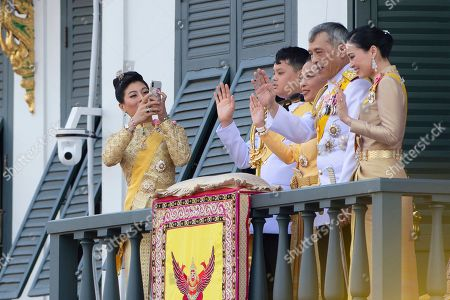 Sirivannavari Nariratana, Dipangkorn Rasmijoti, Bajrakitiyabha, Maha Vajiralongkorn, Suthida. Thailand's royal family from left; Princess Sirivannavari Nariratana, daughter, takes a photo, of the royal family from second left; Prince Dipangkorn Rasmijoti, son, Princess Bajrakitiyabha, daughter, King Maha Vajiralongkorn and Queen Suthida wave to an audience from the balcony of Suddhaisavarya Prasad Hall in the Grand Palace during the coronation ceremony, in Bangkok, Thailand. Vajiralongkorn was officially crowned amid the splendor of the country's Grand Palace, taking the central role in an elaborate centuries-old royal ceremony that was last held almost seven decades ago