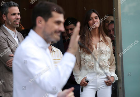 Sara Carbonero watches her husband Spanish goalkeeper Iker Casillas, foreground, speak to journalists outside a hospital in Porto, Portugal, . Veteran goalkeeper Iker Casillas had a heart attack during a training session with his Portuguese club FC Porto and was hospitalized May 1