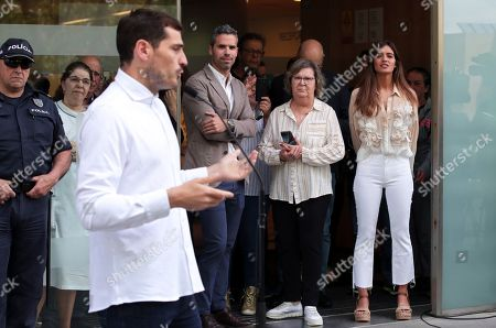 Sara Carbonero, right, watches her husband Spanish goalkeeper Iker Casillas, foreground, speak to journalists outside a hospital in Porto, Portugal, . Veteran goalkeeper Iker Casillas had a heart attack during a training session with his Portuguese club FC Porto and was hospitalized May 1